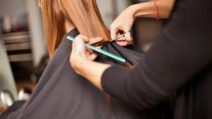 mãos de cabeleireira a cortar cabelo com tesoura