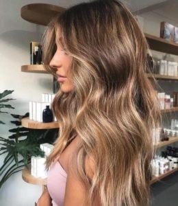 mulher de cabelo longo castanho com madeixas em loja de cosméticos