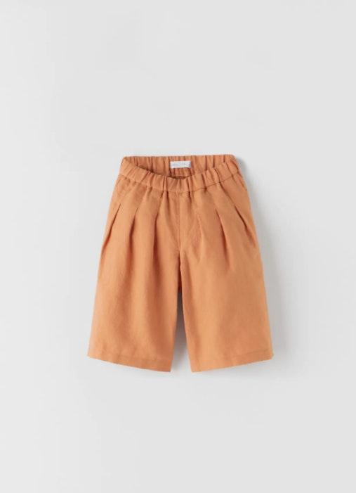 calções de criança laranjas sobre fundo branco