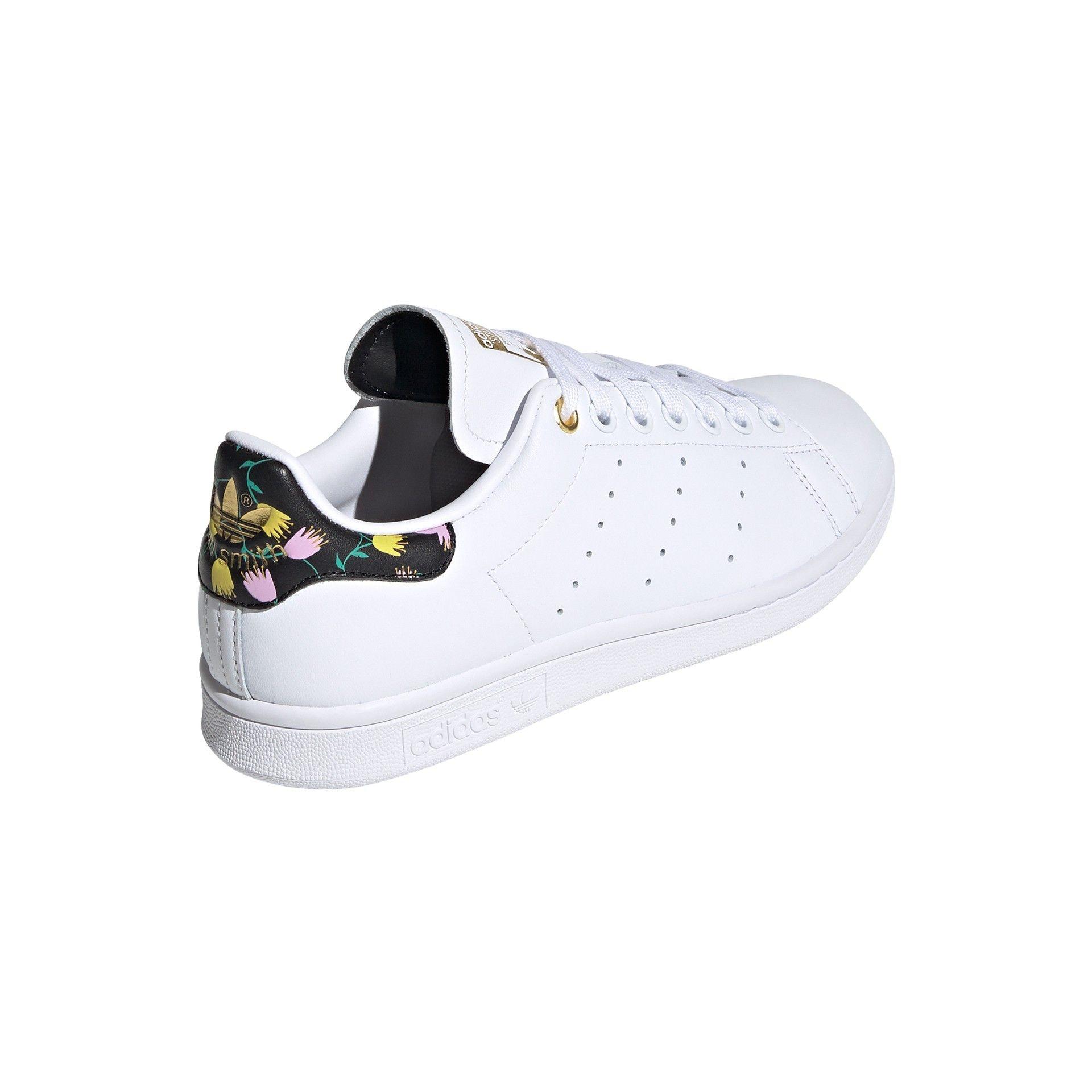 sapatilha branca da adidas com padrão de flores em estúdio sobre fundo branco