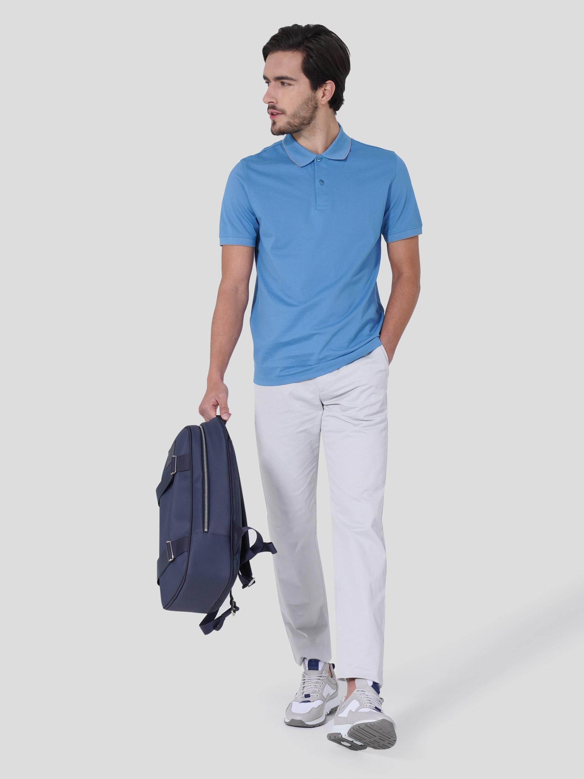 homem moreno de cabelo curto castanho com mão esquerda no bolso e mão direita a segurar uma mochila, vestido com sapatilha e calças cinzentas e polo azul a olhar para o lado