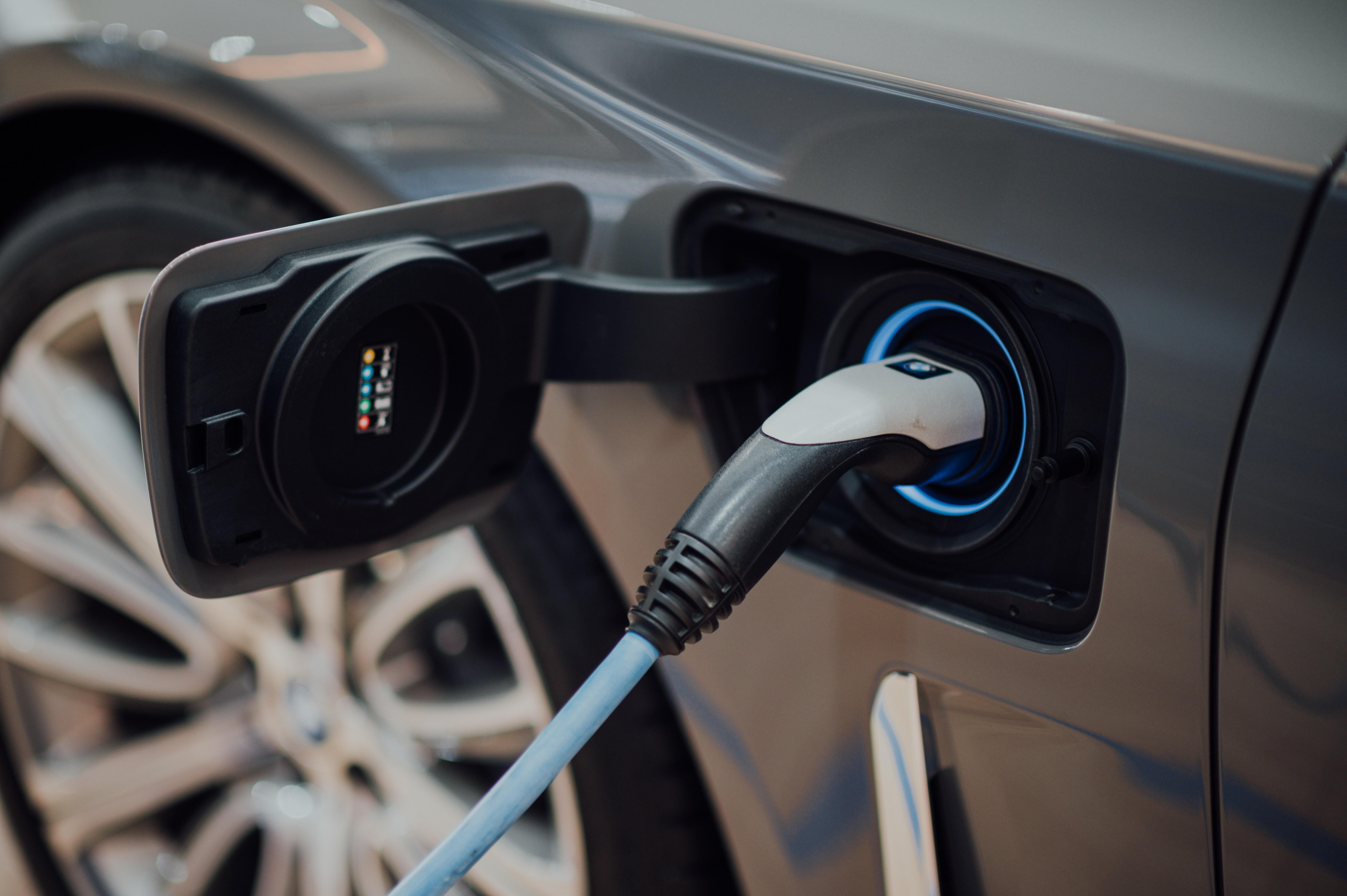 detalhe de carro elétrico a ser carregado