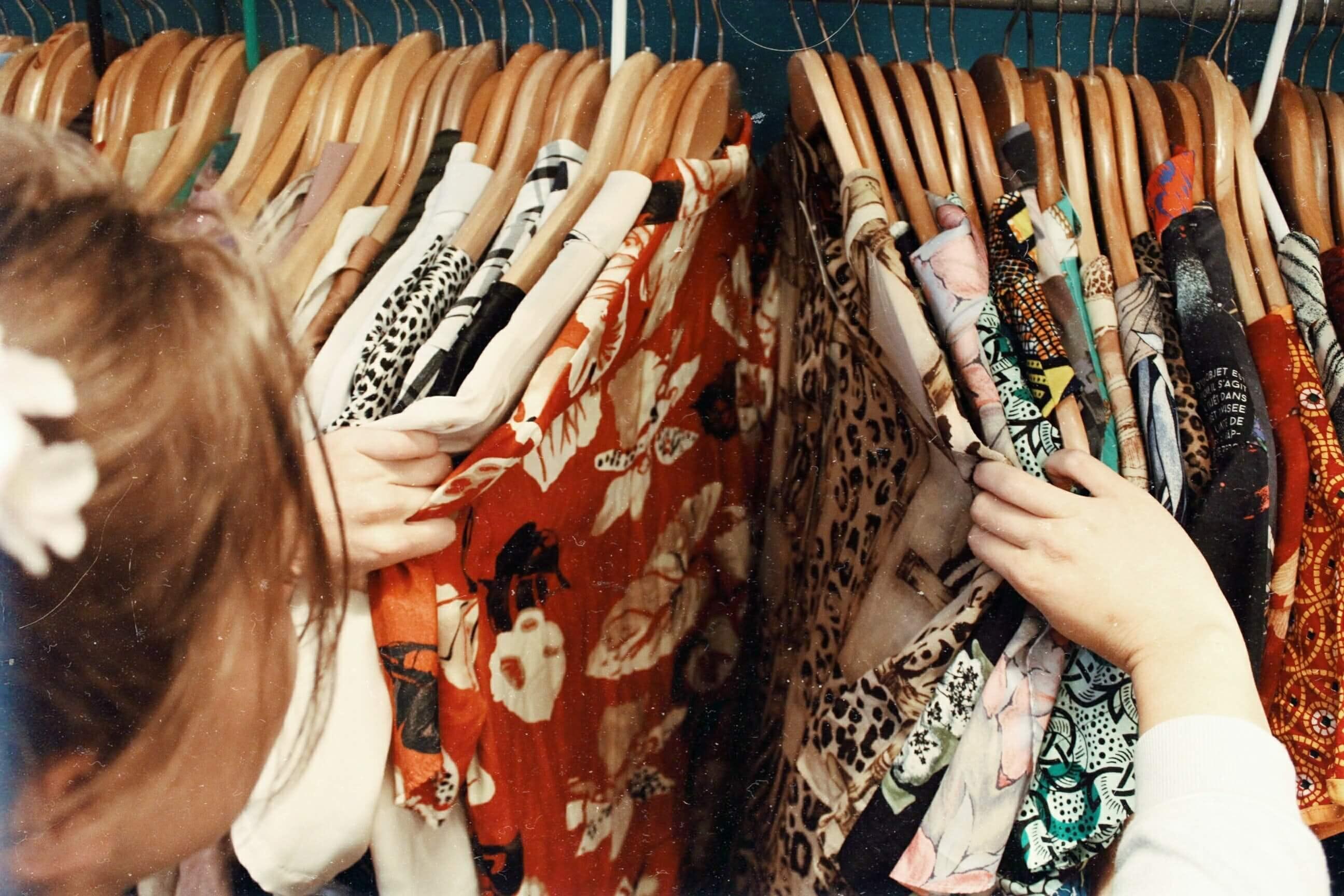 mulher a procurar roupa num cabide de camisas vintage