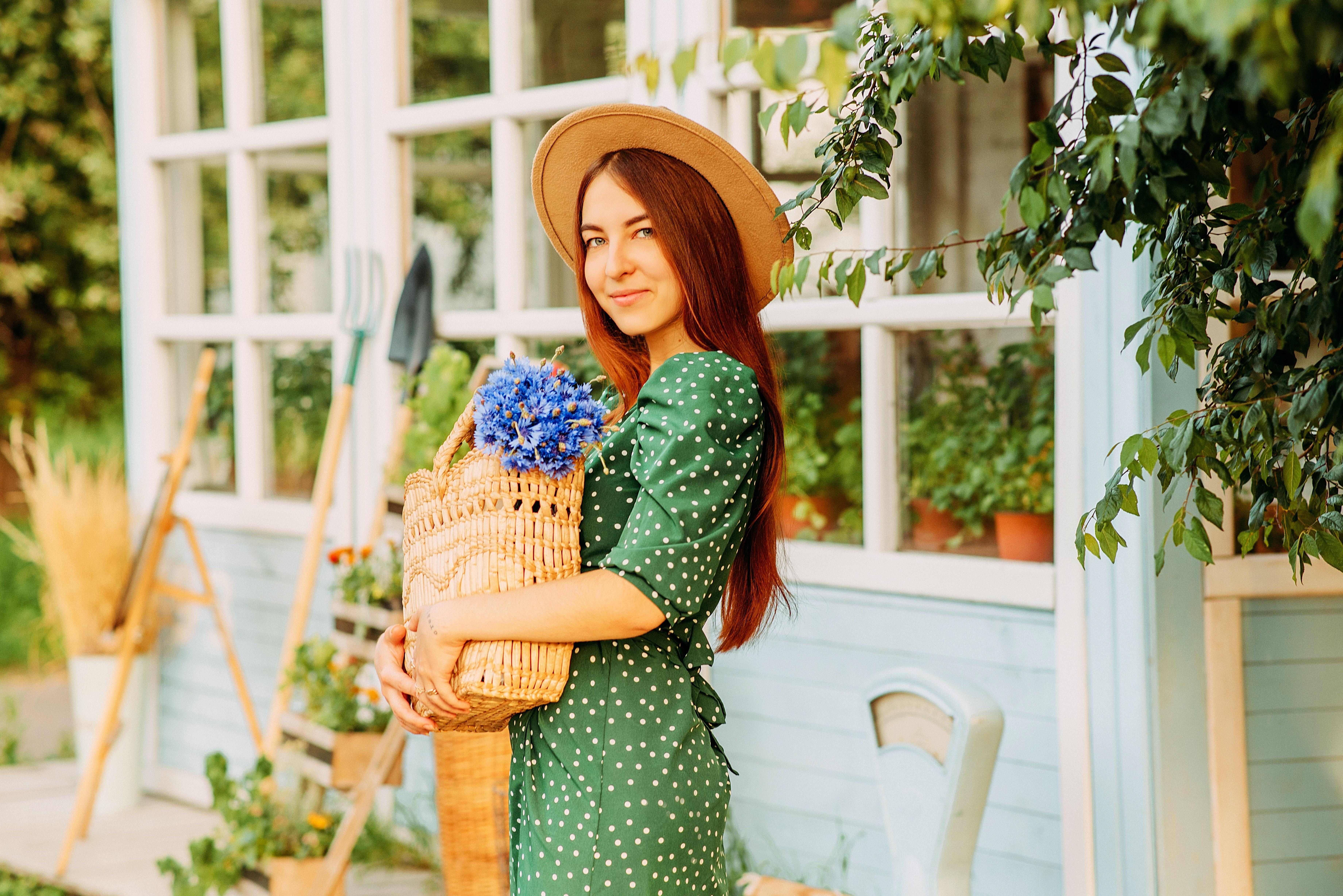 mulher na horta com vestido verde, capéu e um saco de palha com flores na mão