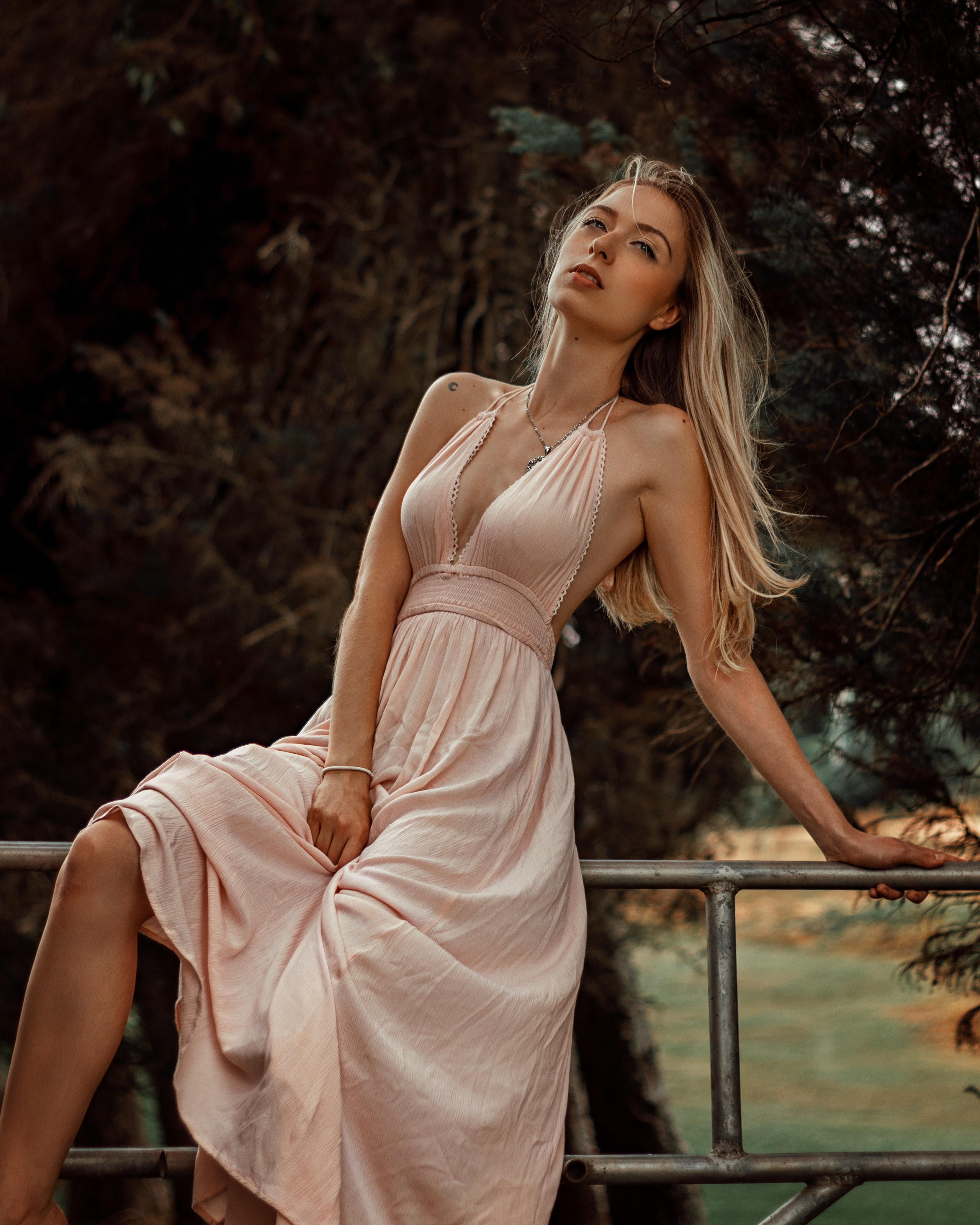 mulher loira de cabelo comprido em sessão fotográfica no exterior vestida com um vestido rosa velho decotado